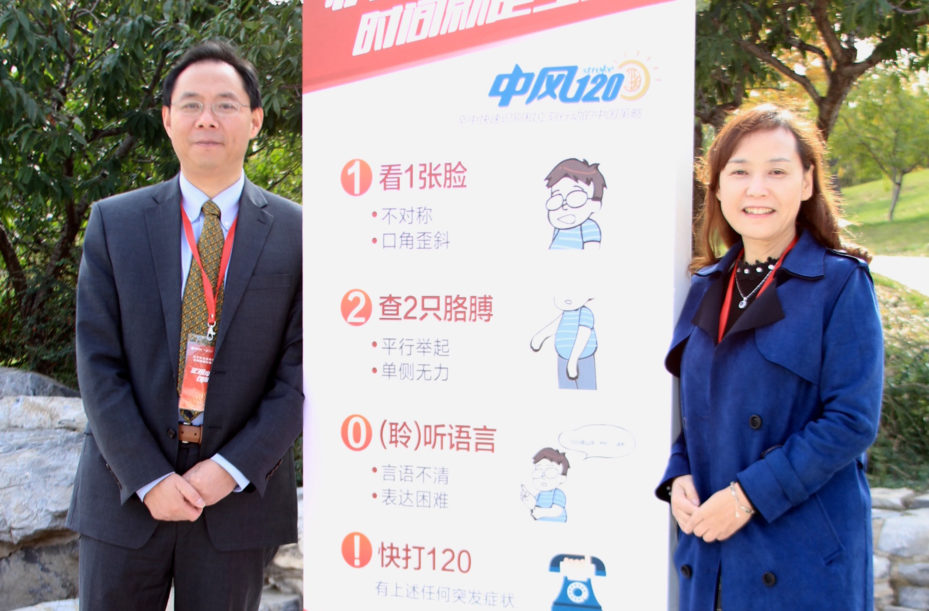 Penn's Renyu Liu (left) and Fudan University's Jing Zhao with a campaign poster for the Stroke 1-2-0 strategy.